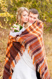 The groom embraces the bride and covers her with a blanket Stock Photo