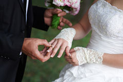 Groom embraces bride, and she holds a bridal bouquet in his hands Stock Photography