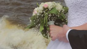 The groom embraces the bride stroking the arm near the sea. Wedding day stock video