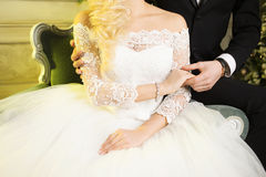 Groom embracing bride from behind. Wedding dress. Hands close-up. Stock Images