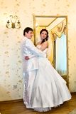 The groom embracing bride near the mirror Stock Image