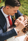 Groom embracing smiling bride on nature Royalty Free Stock Photos