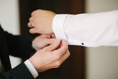 A groom fastening a cuff-link Royalty Free Stock Photo