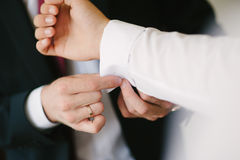 A groom fastening a cuff-link Stock Images