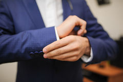 A groom fastening a cuff-link Royalty Free Stock Photography