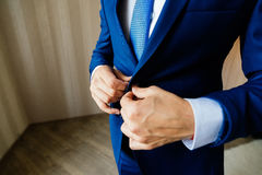 Groom fastens the button on his jacket. The groom fastens the button on his jacket Stock Photo