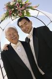 Groom with father under archway outdoors (portrait) Royalty Free Stock Photo