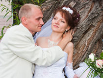 Groom and fiancee in a park. At the barrel of tree Stock Photo