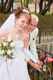Groom and fiancee in a park hang a lock on the bridge of Stock Photography