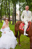 A groom and fiancee sit down on a horse Royalty Free Stock Image