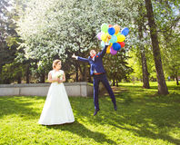 Groom flies on the balloons, but the bride holds his hand. Funny wedding. Groom jumps and flies on balloons. Young Royalty Free Stock Photography