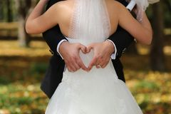Groom forming heart behind bride. Groom forming shape of a heart with hands wrapped around waist of bride on sunny day Stock Image