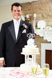 Groom at Gay Wedding. Handsome groom standing beside the wedding cake at his gay wedding, waiting for his husband Stock Photo