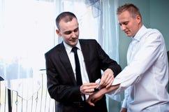 Groom getting dressed. Best men helping groom getting dressed, attending to his sleeves pins royalty free stock photo