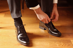 Groom getting his shoes on Royalty Free Stock Image