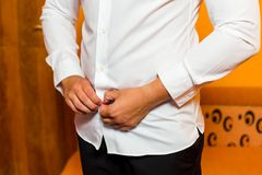 Groom getting ready in the morning. The young man puts on a white shirt, close-up.  Stock Photos