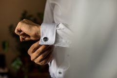 Groom getting ready using cufflinks stock photo