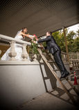 Groom getting up ladder to give flowers to bride on balcony Stock Photo