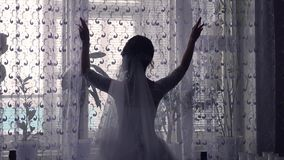 Groom girl opens the curtains in the room by the window silhouette Stock Photo