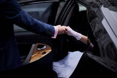 Groom give hands bride out from wedding car Stock Photography
