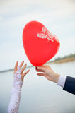 Groom gives a balloon form of heart to bride Royalty Free Stock Photos