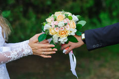 Groom gives bride a wedding bouquet in summer park Royalty Free Stock Photos
