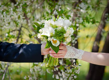 Groom gives the bride a wedding bouquet of white flowers.  Stock Photography