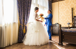 Groom giving bouquet to his bride Stock Image