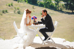 Groom Giving Bride Bouquet at Table. Groom giving bride blue rose bouquet at table Stock Photos
