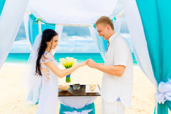 Groom giving an engagement ring to his bride under the arch deco Stock Images