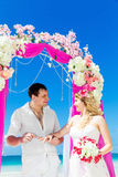 Groom giving an engagement ring to his bride under the arch deco Stock Photography