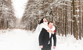 Groom giving piggyback ride to bride in winter woods Stock Photos