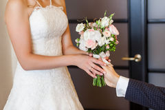 Groom giving wedding bouquet to his bride Stock Photography