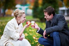 Groom with glass brandy, and bride with red apple Royalty Free Stock Photo