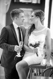 Groom with a glass of champagne and the bride with a bouquet from roses Stock Photography