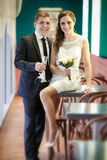 Groom with a glass of champagne and the bride with a bouquet from roses Royalty Free Stock Photo