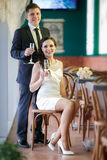 Groom with a glass of champagne and the bride with a bouquet from roses Royalty Free Stock Photography