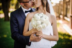 Groom with glasses is going to kiss the charming bride in a white dress. Stylish groom with glasses is going to kiss the charming bride in a white dress, with a Stock Photography