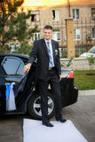 Groom goes out of the car on a white path for  a wedding ceremony Royalty Free Stock Image