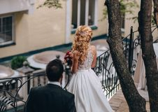 Groom goes bride blonde near railing back stock photos