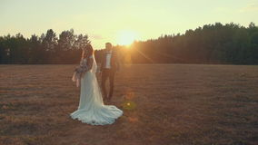 Groom goes to bride holding bouquet on grass in rays of setting summer sun. stock video footage