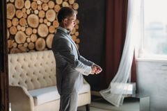 The groom is going on a wedding day, puts on a jacket and straightens the sleeves. Classical business clothes for work. Or office. Businessman in gray suit and royalty free stock images