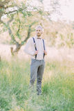 The groom in the gray pants and white shirt holding his black suspenders in the green spring field. The groom in the gray pants and white shirt holding his Royalty Free Stock Photography