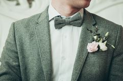 A groom in grey suit and white shirt preparing for the event. Light background Royalty Free Stock Image