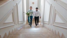 Groom and groomsman going upstairs stock footage