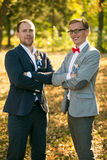 Groom and groomsman posing at autumn park Stock Images