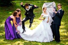 Groom and groomsmen jump behind pretty ladies Royalty Free Stock Photos