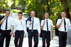 Groom and groomsmen walk proud holding their jackets over should. Ers Stock Images