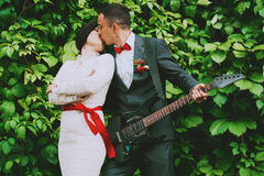 Groom with guitar kissing bride Royalty Free Stock Photo