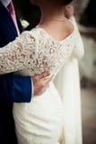 Groom hand on brides dress Royalty Free Stock Photos